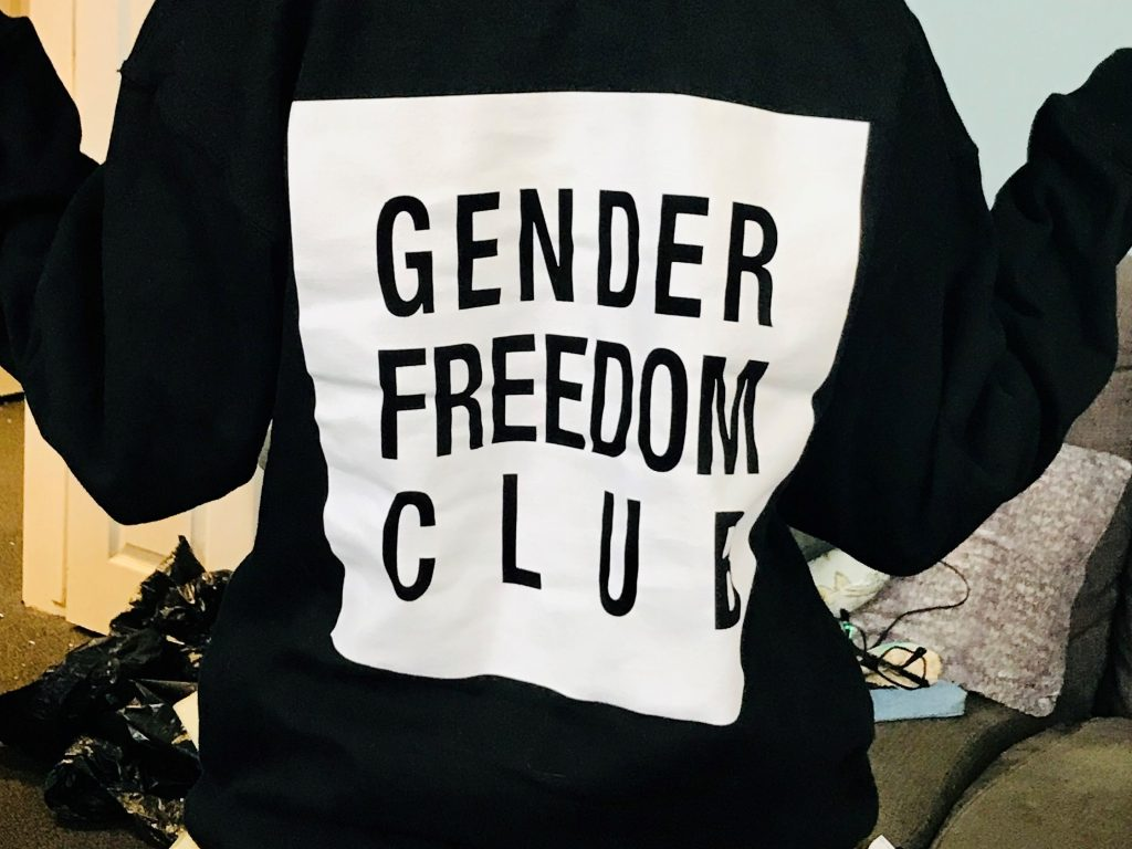 "Photo of the back of a black sweatshirt with a large white square. Filling the white square is black text in all caps which reads, ""gender freedom club"""