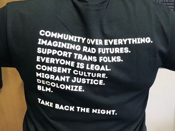 "Photo of the back of a black t-shirt with white text in all caps reading, ""community over everything. imaging rad futures. support trans folks. everyone is legal. consent culture. migrant justice. decolonize. blm. take back the night."""